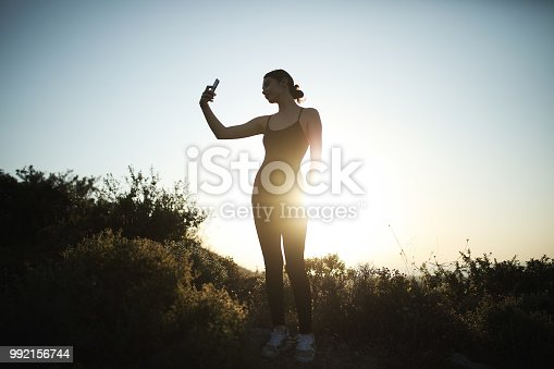 628497270 istock photo Young woman holding smart shone looking away 992156744