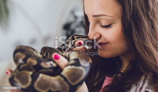 Young woman holding pet ball python at home