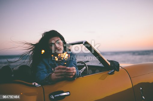 Young hipster woman sitting in vintage cabriolet car holding sparklers and day dreaming at beach