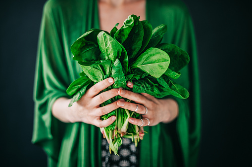 istock Young woman holding spinach leafs salad 477423372