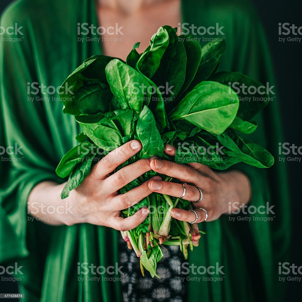 Young woman holding spinach leafs salad stock photo