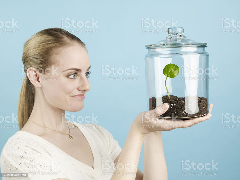 Young woman holding sprouting plant in glass jar, studio shot royalty-free stock photo