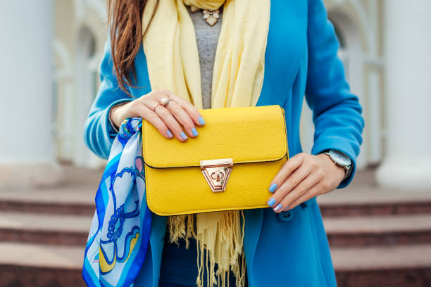 young woman holding stylish handbag and wearing trendy blue coat. spring female clothes and accessories. fashion - spring fashion stock pictures, royalty-free photos & images