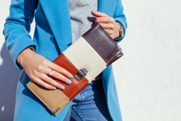 Young woman holding stylish handbag and wearing trendy blue coat. Spring female clothes and accessories. Fashion stock photo