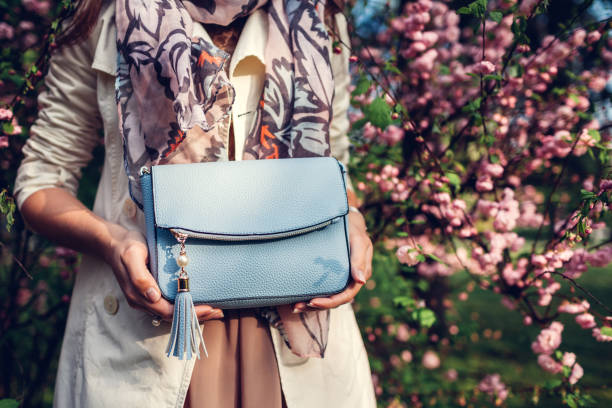Young woman holding stylish handbag and wearing trendy outfit. Spring female clothes and accessories. Fashion stock photo