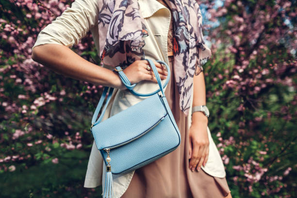young woman holding stylish handbag and wearing trendy outfit. spring female clothes and accessories. fashion - borsetta foto e immagini stock