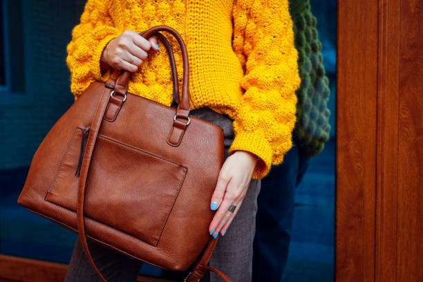 young woman holding stylish handbag and wearing yellow sweater. spring female clothes and accessories. fashion - borsetta foto e immagini stock