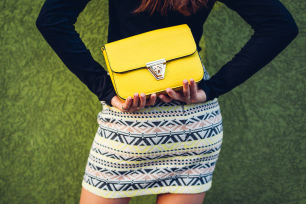 Young woman holding stylish yellow handbag. Spring female clothes and accessories. Fashion stock photo