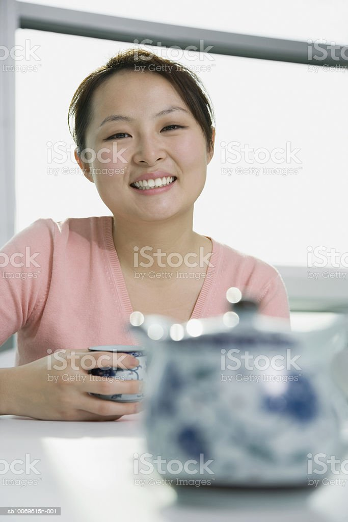 Young woman holding tea cup, smiling, portrait foto de stock libre de derechos