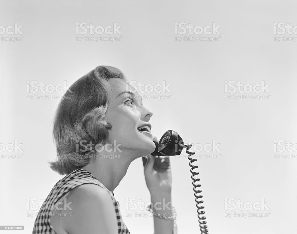 Young woman holding telephone receiver, smiling stock photo