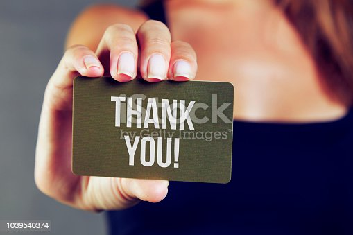 1094837778 istock photo Young woman holding thank you card 1039540374