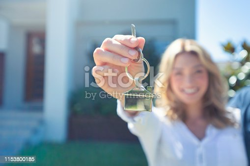 Young woman holding the key to her new house. She is smiling and happy. They keyring is shaped like a house. The house can be seen in the background.