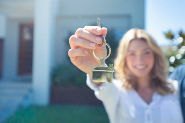 young woman holding the key to her new house. - buy a house key imagens e fotografias de stock