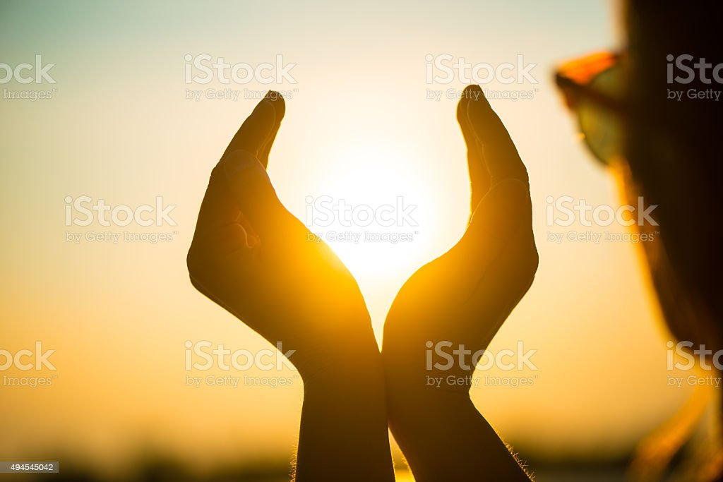 young woman holding the sunset in her hands stock photo