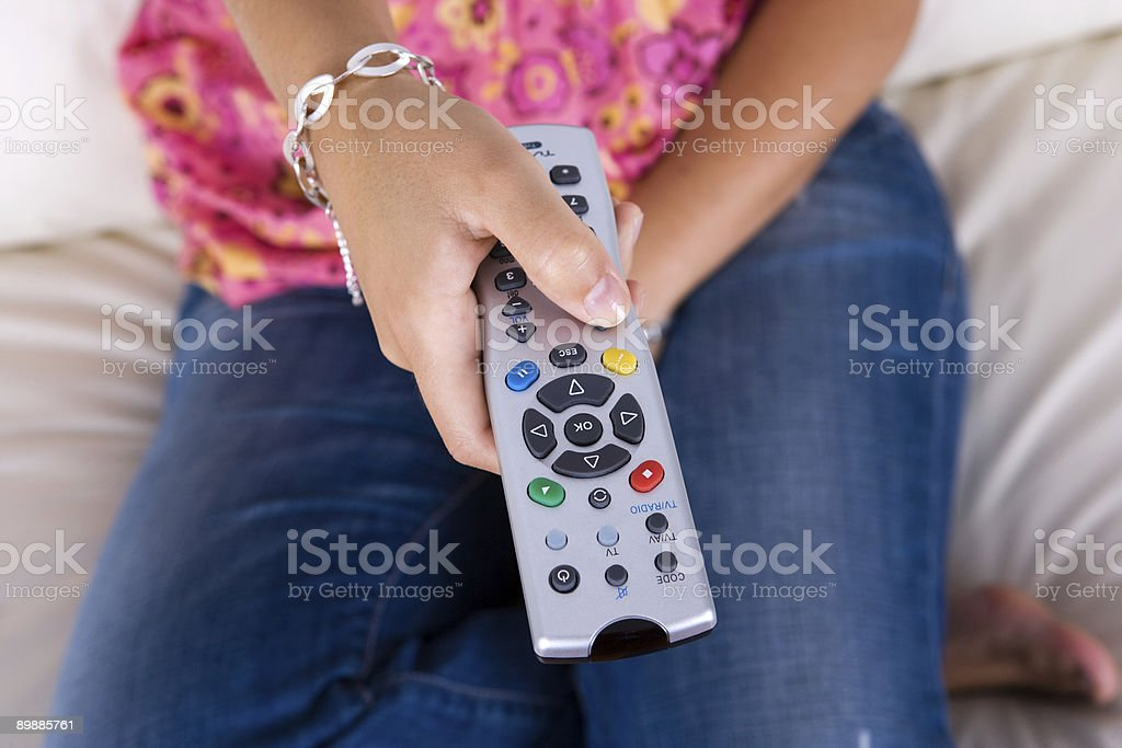 young woman holding the television remote control royalty-free stock photo
