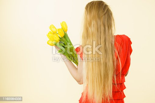 Shot of young woman holding romantic yellow tulip bouquet. Women day gift. Studio shot on light background.