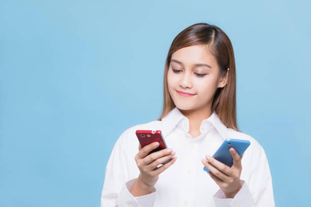 Jovem mulher segurando dois telefones inteligentes. - foto de acervo