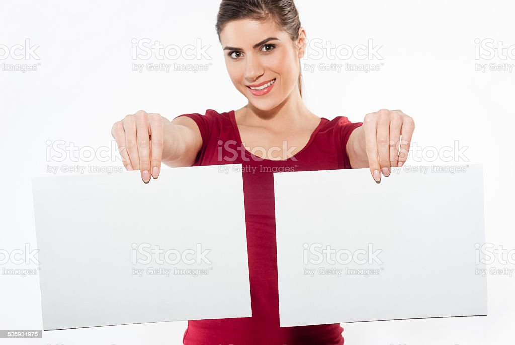 Young woman holding two white papers with copy space stock photo