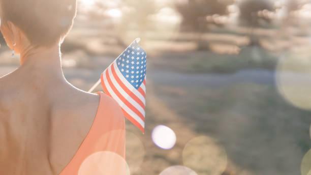 Mulher nova que prende a bandeira dos EUA - foto de acervo