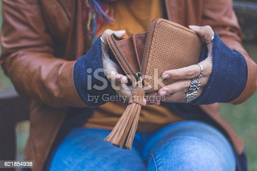 istock Young woman holding wallet outdoors in autumn park 621854938