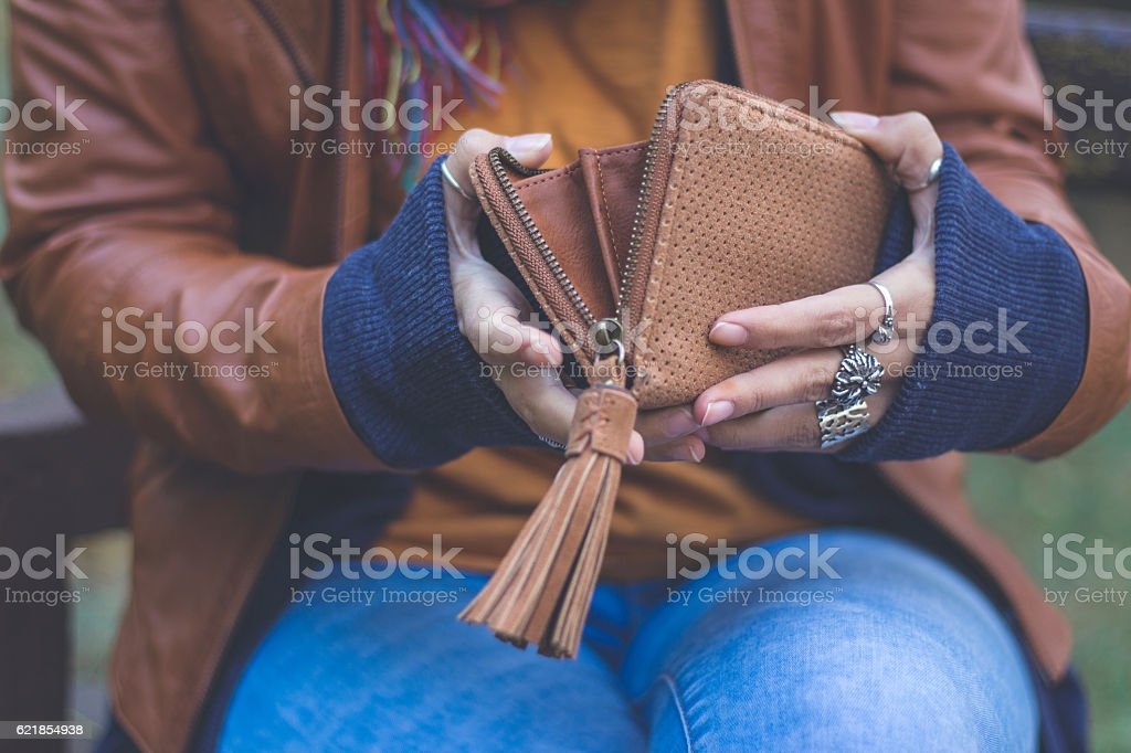 Young woman holding wallet outdoors in autumn park stock photo