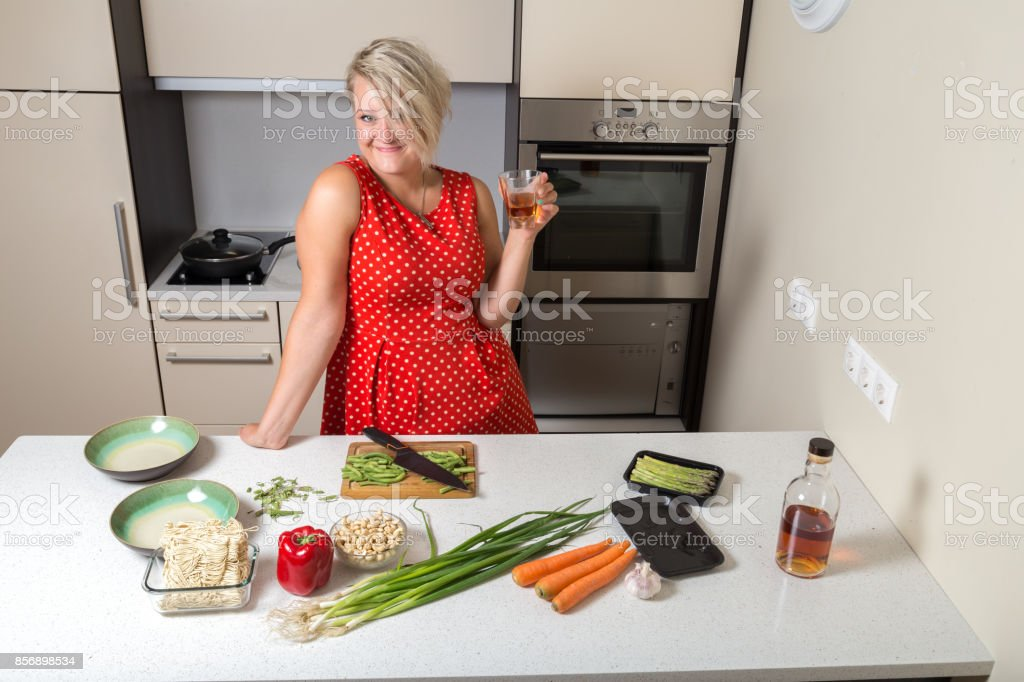 Young woman holding whiskey glass in hand and smiling stock photo