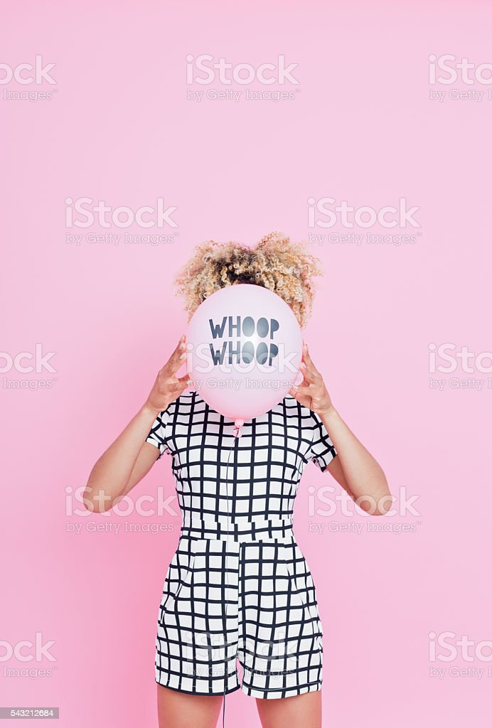 Young woman holding WHOOP WHOOP balloon Portrait of unrecognisable young woman, wearing grid check playsuit, standing against pink background and hide her face behind WHOOP WHOOP Balloon. 2016 Stock Photo