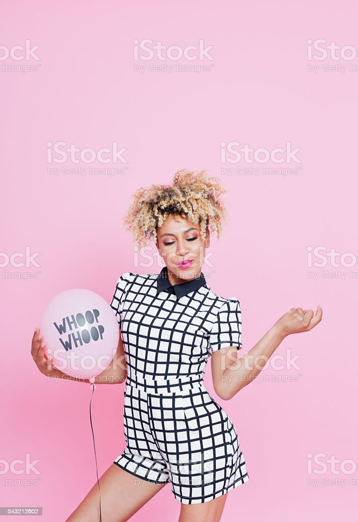 Young woman holding YAY balloon Portrait of young woman, wearing grid check playsuit, dancing against pink background and holding WHOOP WHOOP Balloon. 20-29 Years Stock Photo