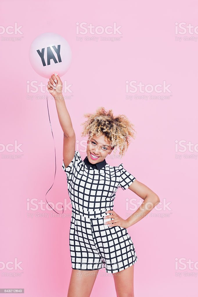 Young woman holding YAY balloon Portrait of young woman, wearing grid check playsuit, standing against pink background and holding YAY Balloon above here head. 20-29 Years Stock Photo