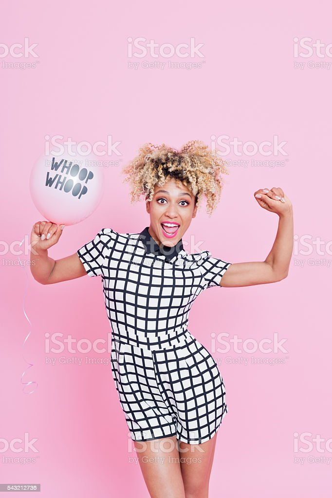 Young woman holding YAY balloon Portrait of young woman, wearing grid check playsuit, dancing against pink background with WHOOP WHOOP Balloon. 20-29 Years Stock Photo