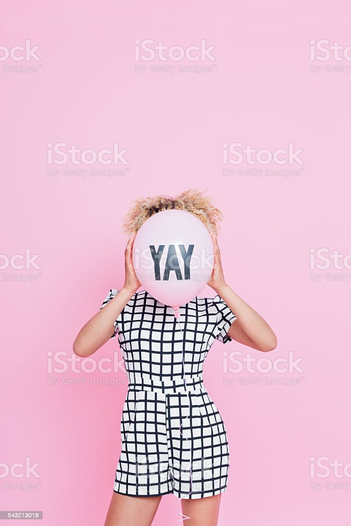 Young woman holding YAY balloon Portrait of unrecognisable young woman, wearing grid check playsuit, standing against pink background and hide her face behind YAY Balloon. 2016 Stock Photo