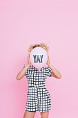 Portrait of unrecognisable young woman, wearing grid check playsuit, standing against pink background and hide her face behind YAY Balloon.