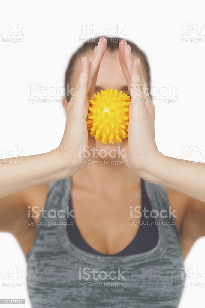 Young woman holding yellow massage ball between hands stock photo
