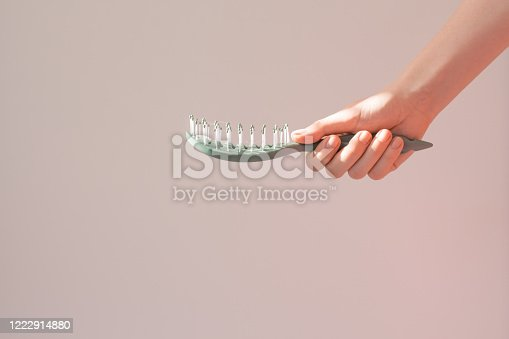 istock Young woman holds a hairbrush mock up with the shadow of a plant. Problems with stripes, dandruff, itching. Minimalism 1222914880