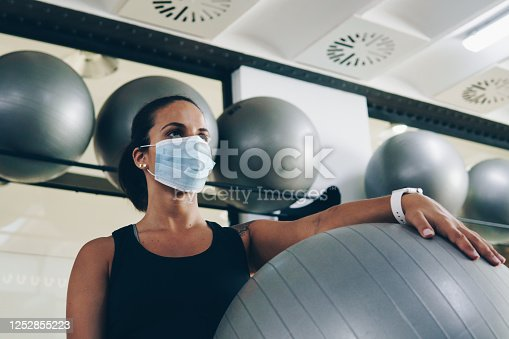 Young woman holds a pilates ball in the gym. She's wearing a mask.