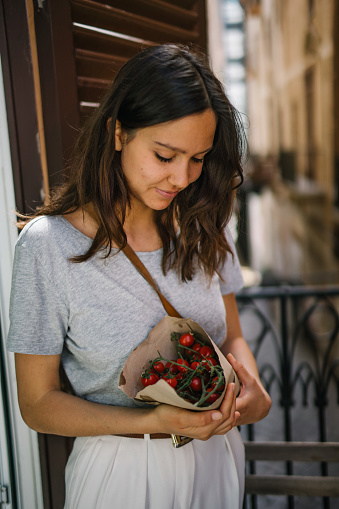 Young woman holds bouquet of fresh tomatoes on household  balcony