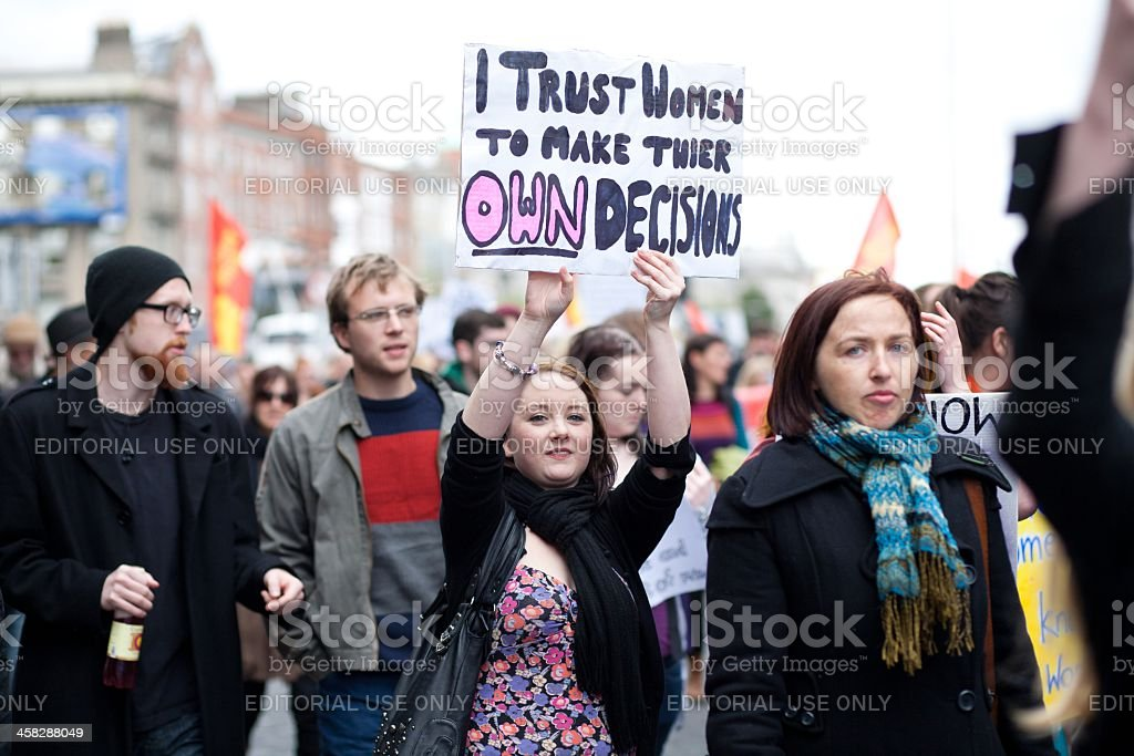 Young woman holds hand made poster about women decisions stock photo
