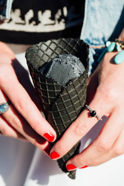 young woman holds in hands dark black cone ice-cream. close-up portrait female with red lips - nails ice cream imagens e fotografias de stock