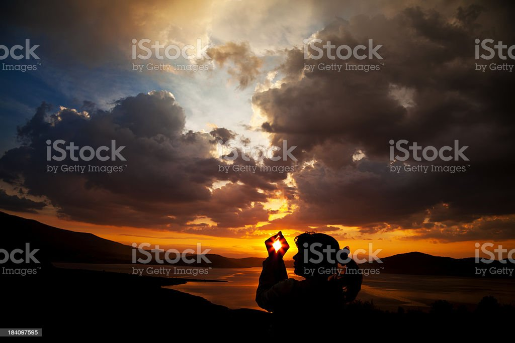Young Woman Holds the Sun in Her Hands royalty-free stock photo