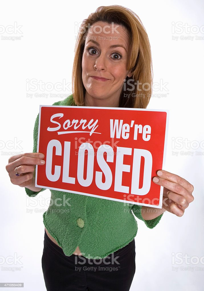 Young woman holds up 'Sorry We're Closed' sign royalty-free stock photo