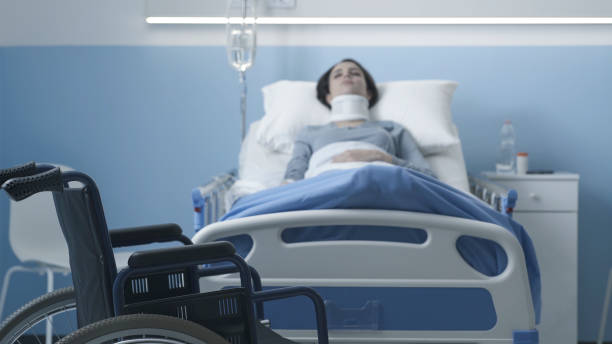 Young woman hospitalized after a serious accident Young woman lying in a hospital bed after a serious accident, wheelchair in the foreground paraplegic stock pictures, royalty-free photos & images