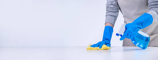 young woman housekeeper is doing cleaning white table in apron with blue gloves, spray cleaner, wet yellow rag. - propre photos et images de collection