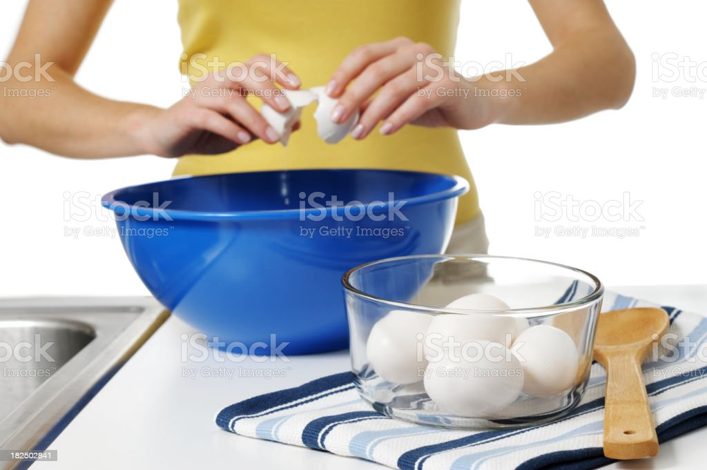 Young Woman Housewife Breaking Eggs Isolated on White Background royalty-free stock photo