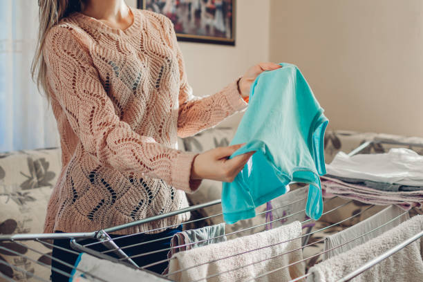 Young woman housewife hanging clean clothes on dryer after washing at home. Housekeeping and household chores Young woman housewife hanging clean wet clothes on dryer after washing at home in living room. Housekeeping and household chores wet clothing women t shirt stock pictures, royalty-free photos & images