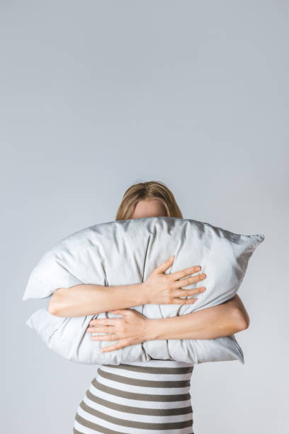 Young woman hugging a gray pillow stock photo