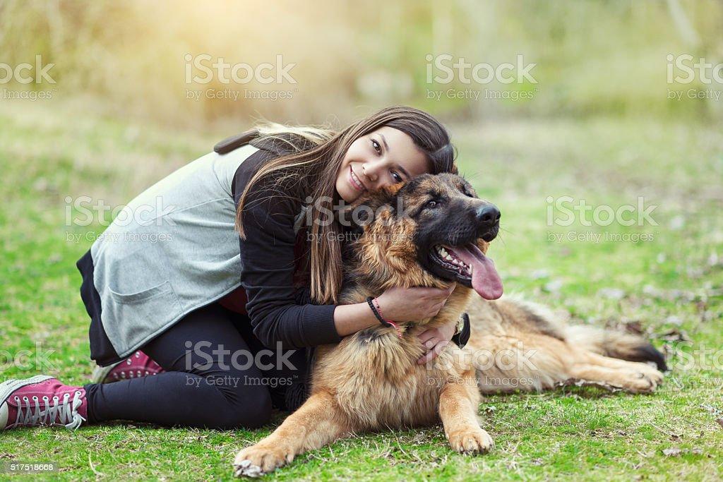 Jeune femme embrassant son Berger allemand dans le parc - Photo