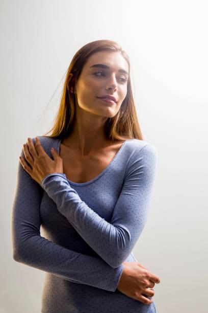 Jeune femme étreignant elle-même tout en regardant loin - Photo