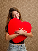Young woman hugging red heart shape