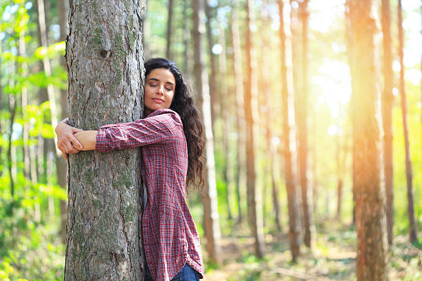 Young woman hugging tree in woodland Cheerful young woman hugging tree in the forest. Standing, eyes closed. Trees and sun on background. tree hugging stock pictures, royalty-free photos & images