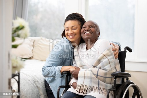 A daughter puts her arms around a smiling mother wrapped up in a blanket, sitting in a wheelchair.